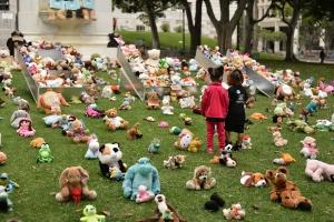Children walking among dozens of teddy bears